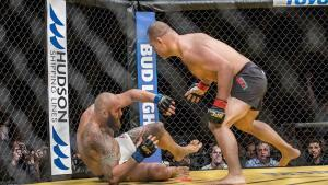 Cain Velasquez Jumps On The Rocked Travis Browne.