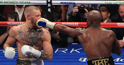 Floyd Mayweather Jr punches Conor McGregor.