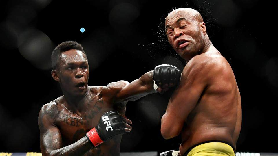 Israel Adesanya lands a left punch on Anderson Silva in their fight.