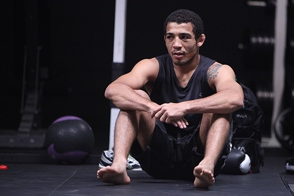 Jose Aldo junior sits in the cage.
