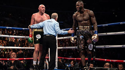 Tyson Fury sticks tongue out to Deontay Wilder in their fight.