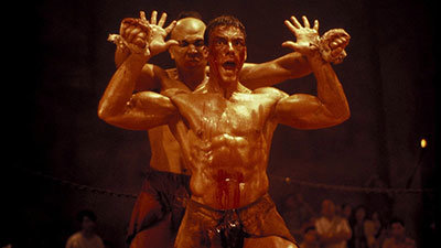 Eric Sloane played by Jean Claude Van Damme blocks an attack by Tong Po in kickboxer fight scene.