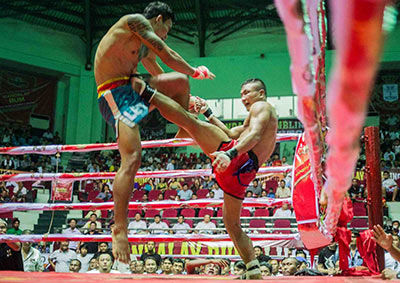 Two Lethwei fighters go toe to toe inside the ring.