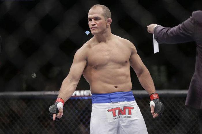Junior Dos Santos inside the UFC Octagon pointing to the ground.