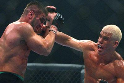 Tito Ortiz (blonde hair) lands a right hand punch against Ken Shamrock.