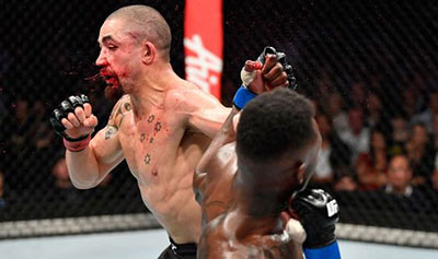 Robert Whittaker takes a hard shot from challenger Israel Adensanya in Melbourne.